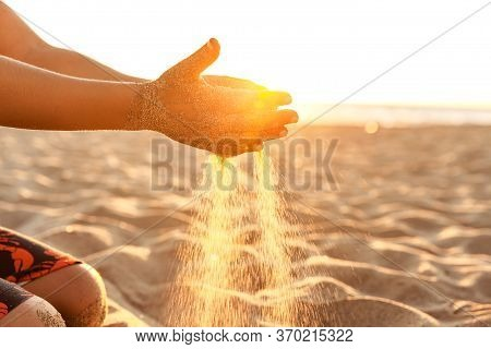 Little Boy Playing With Sand On The Beach At Sunset In California, Closeup Of Hands At Natural Sunli
