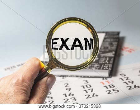 Magnifying Glass With The Word Exam On Book Of Maths Or Physics On Calendar Sheets On Blue Table. Se