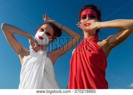 Two Beautiful Young Brunette Girls With Creative Bright Makeup In Tunics Against A Blue Sky In A Mas