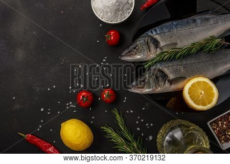 Two Fresh Seabass Fishes With Rosemary And Vegetable On A Black Plate. Seafood Concept.
