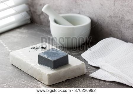 Handmade Soap With Activated Carbon On Marble, Carbon Powder And A Cotton Towel On A Gray Background