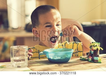 The Boy 4 Years Eats Porridge. Childrens Table. The Concept Of The Childs Independence. The Boy Is B