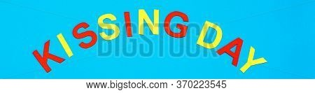 World Kiss Day. Lettering Kissing Day Made Of Colored Cardboard On A Blue Background. Web Banner