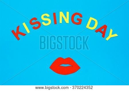 World Kiss Day. Red Lips And The Inscription Kissing Day Made Of Cardboard On A Blue Background.