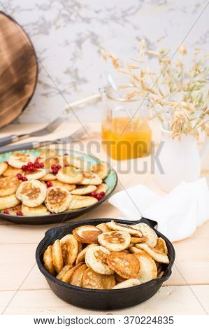 Trend Breakfast. Dutch Mini Pancakes In A Pan And On A Plate With Red Currants On A Wooden Table. Ve