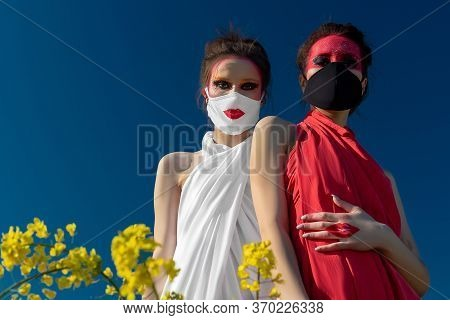 Two Beautiful Young Brunette Girls With Creative Bright Makeup In Tunics On A Background Of A Field