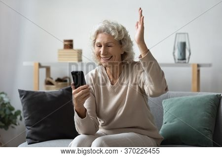 Excited Elderly Woman Triumph Reading News On Cell