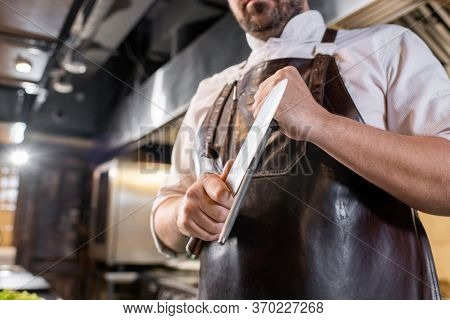 Close-up of professional chef using honing rod for sharpening kitchen knife at workplace