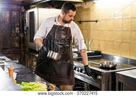 Portly chef in leather apron choosing stove temperature while turning on it at commercial kitchen