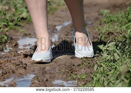 Female Feet On A Muddy Path, Shoes Soiled In Mud. Rural Street With Puddles After Rain In Summer, Wo