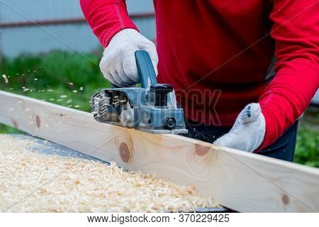 A Man's Hand Holds An Electric Planing Tool . The Carpenter Does The Hardest Work. Profession Of Car