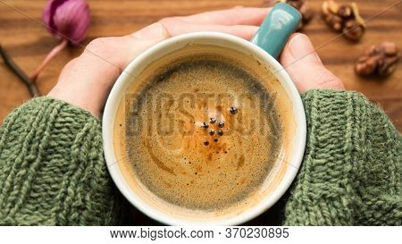 A Mens Hands Are Holding A Cup Of Aromatic Coffee. A Cup Of Aromatic Coffee Stands On A Wooden Table