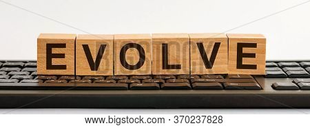 Word Evolve Written On Wooden Cubes On Black Keyboard Background. Evolve Word Made With Building Blo