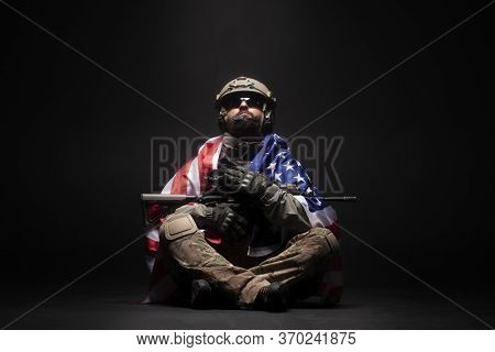 American Commando In Military Equipment And With Arms Sits And Holds The Usa Flag, A Modern Ranger L