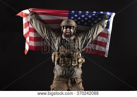 American Commando In Military Equipment Holds Usa Flag At Night, Modern Ranger Screams In The Dark,