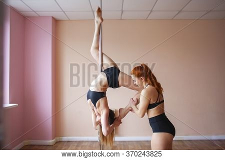 Pole Dance Training, Girl Trainer Teaches A Student A Gymnastic Trick, Pole Dance School, Copy Space