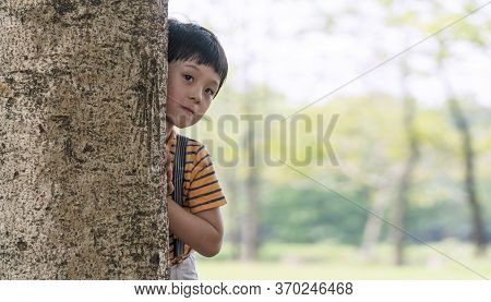 The Mixed Race Boy Hides Behind A Tree In The Park. Little Cute Child Looks Out From Behind Tree, Pl