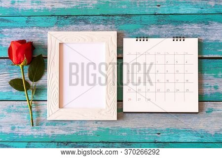 Blank Photo Frame, Calendar And Red Roses Over Wooden Table