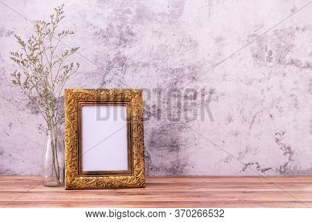 Picture Frame With Flowers On Wall Background And Wooden Table. Poster Product Design Styled