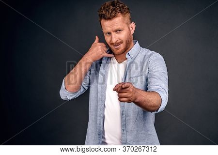 Young Attractive Guy With Red Hair In Casual Shirt, Makes Phone Sign, Indicates With Index Finger Di