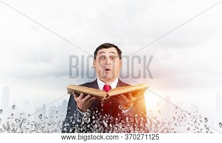 Surprised Businessman Holding Open Old Book. Portrait Of Startled Man In Business Suit And Tie Stand