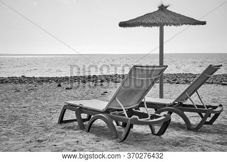 Beach with parasol and chaise longues by the sea - Black and white photography