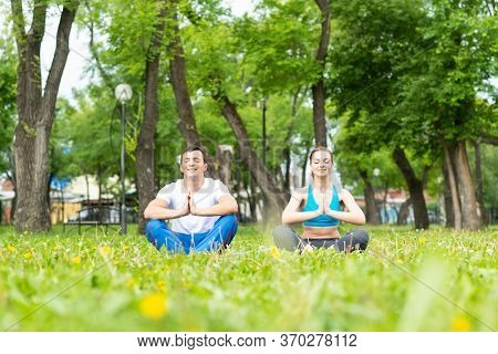 Couple Of Young Sporty People Practicing Yoga. Man And Woman With Closed Eyes Doing Yoga In Park Tog