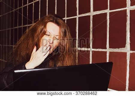 A Woman With Shaggy Red Hair Sits With A Laptop And Yawns. The Concept Of Remote Work. Close Up.