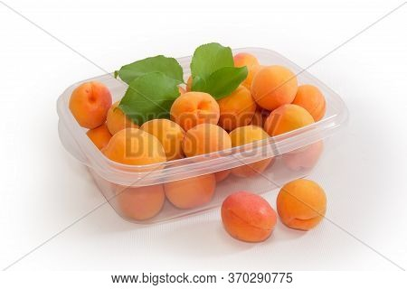 Ripe Apricots With Several Apricot Leaves In The Plastic Food Container And Two Apricots Separately