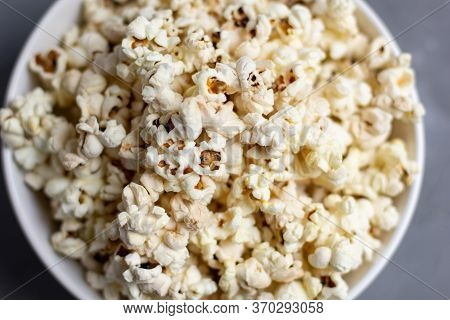 Popcorn In White Bowl On Grey Table. Top View With Copyspace