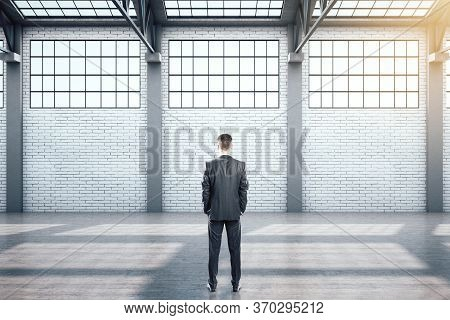 Businessman Standing In Contemporary Warehouse Interior With Window And Daylight. Industrial And Exh