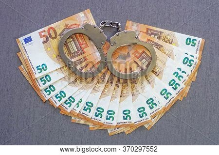 Handcuffs On The Background Of 50 Euro Isolated On A Gray Background. Fan Of 50 Euro Banknotes. Fan