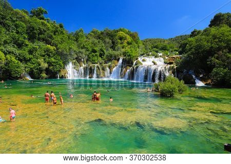 Tourists Swim In The Lake Near Picturesque Cascade Waterfall In The Krka National Park, Croatia In S
