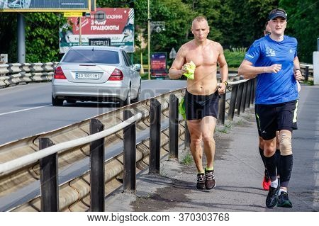 Uzhgorod, Ukraine - June 7, 2020: A Group Of Young People Run Across The Bridge While Relaxing Quara