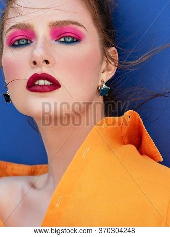 Fashion Portrait Of Stunning Woman With Bright Makeup  And Fluttering Hair Wearing Orange Shirt. Sen