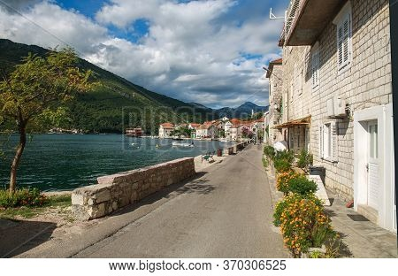 Old Town Settlement Around The Lake, Kotor Bay, On The Background Of Blue Sky And Clouds, Montenegro
