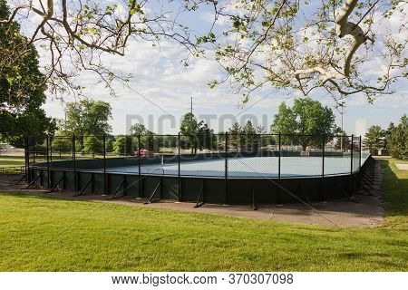 A Side View Of An Unoccupied Roller Hockey Rink In A City Park