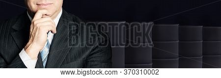 Smart Businessman With Crude Oil Barrels On Black Background. Crude Oil And Petroleum Industry Conce