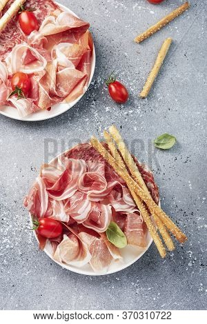 Traditional Italian Antipasto With Ham, Salami And Bread Sticks, Selective Focus Image
