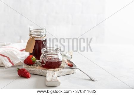 Homemade Strawberry Jam Or Marmalade In The Glass Jars And Ripe Strawberries On The Wooden Board On