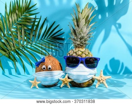 Coconut And Pineapple With Sunglasses In Medical Masks And Sea Stars Among Palm Leaves On Blue Backg
