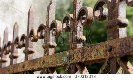 A Rusted, Decorated, Wrought Iron Fence. Detail Of An Old Retro Iron Fence Made With Decorated Ironw