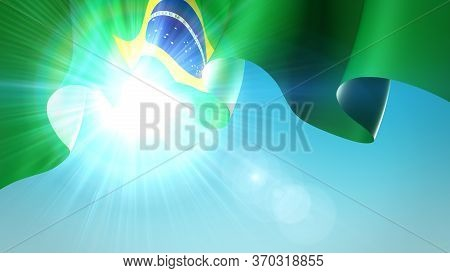 The Sun Shines With Golden Rays Through The Waving Flag Of Brazil. Brazil Waving Flag On Blue Sky Fo