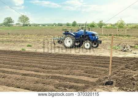 A Farm Tractor Is Standing On The Field. Preparing The Land For Planting Future Crop Plants. Cultiva