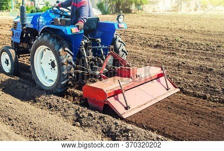Farmer On A Tractor Cultivates Land After Harvesting. Grinding Loosening Plowing Crumbling Soil For