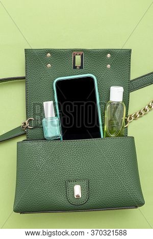 Handbag, Phone, Nail Polish  And Disinfection; Gel On Green Background. Monochrome. Minimal.  vertic