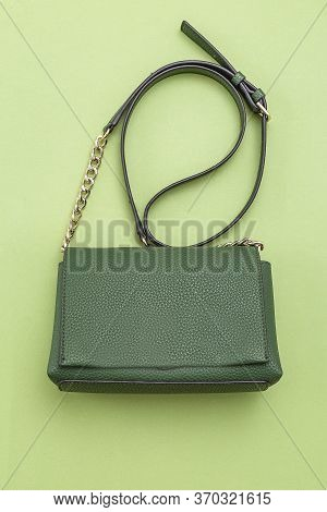 Handbag Green Color On Green Background.  Monochrome. Vertical Format. Feminine Accessories