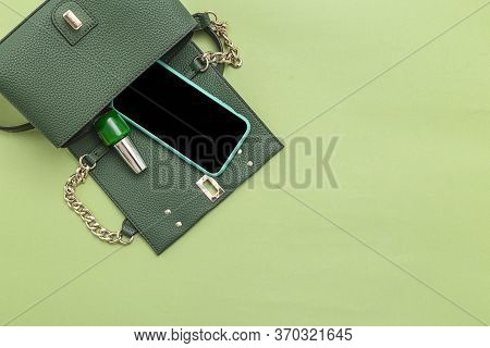 Handbag, Phone, Nail Polish On Green Background. Monochrome. Minimal. Copy Space