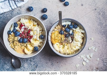 Oatmeal Porridge Bowl With Banana, Berries, Hemp Seeds And Coconut Slices. Healthy Vegan Breakfast C