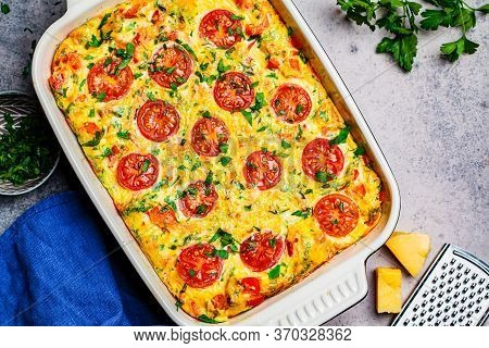 Traditional Egg Frittata With Tomatoes And Cheese In The Oven Dish, Top View. Baked Omelet With Vege